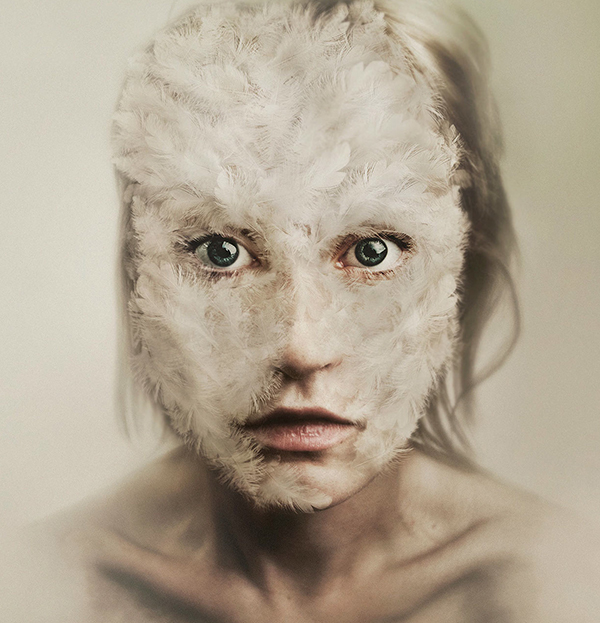 Image of a woman's face covered in feathers, by artist Flora Borsi