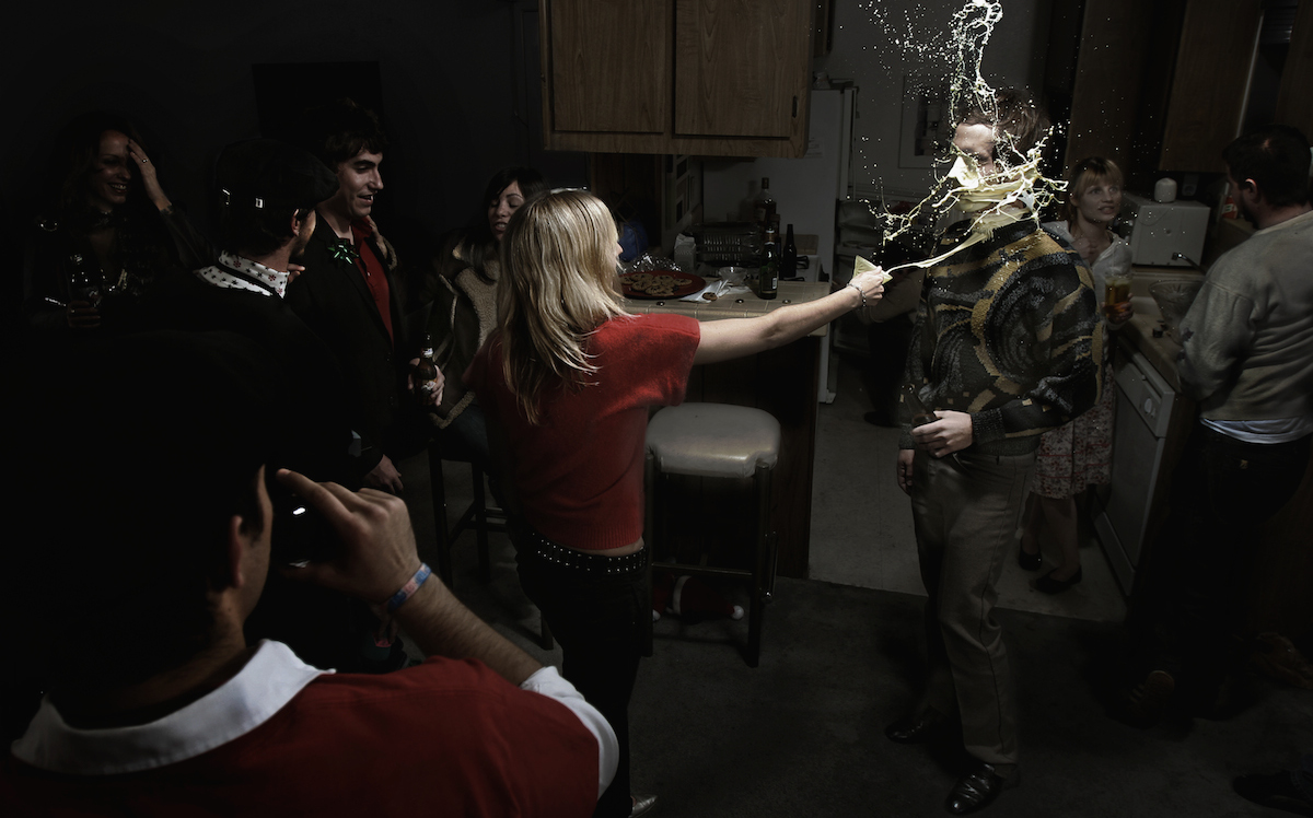 Photo composite by Ryan Schude, image of a woman throwing eggnog in a man's face at a holiday party.