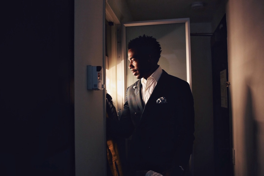 Photo of a lit man looking at an isolated light source, by Aundre Larrow