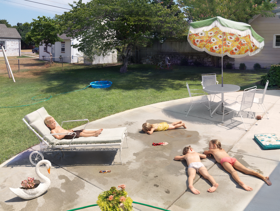 Photograph by Julie Blackmon, of kids sunbathing by a pool.