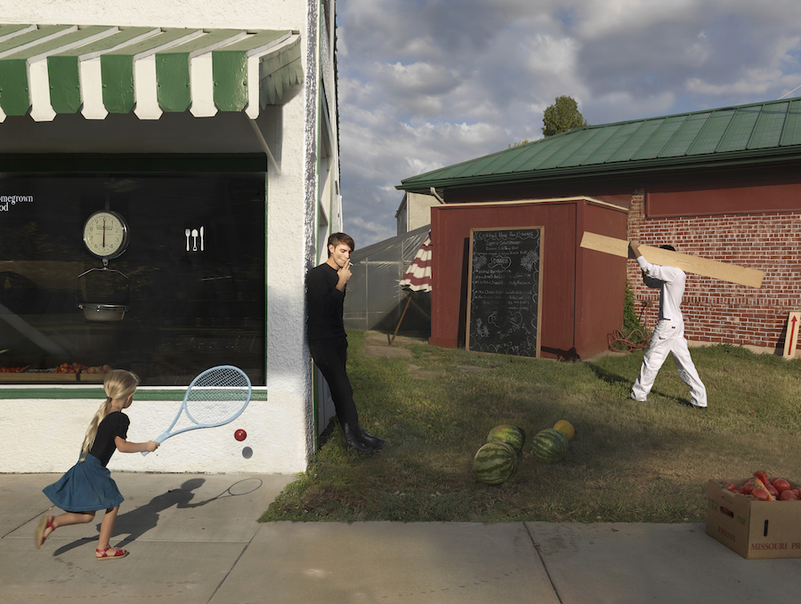 photograph by Julie Blackmon, of a child playing and a teenager smoking.