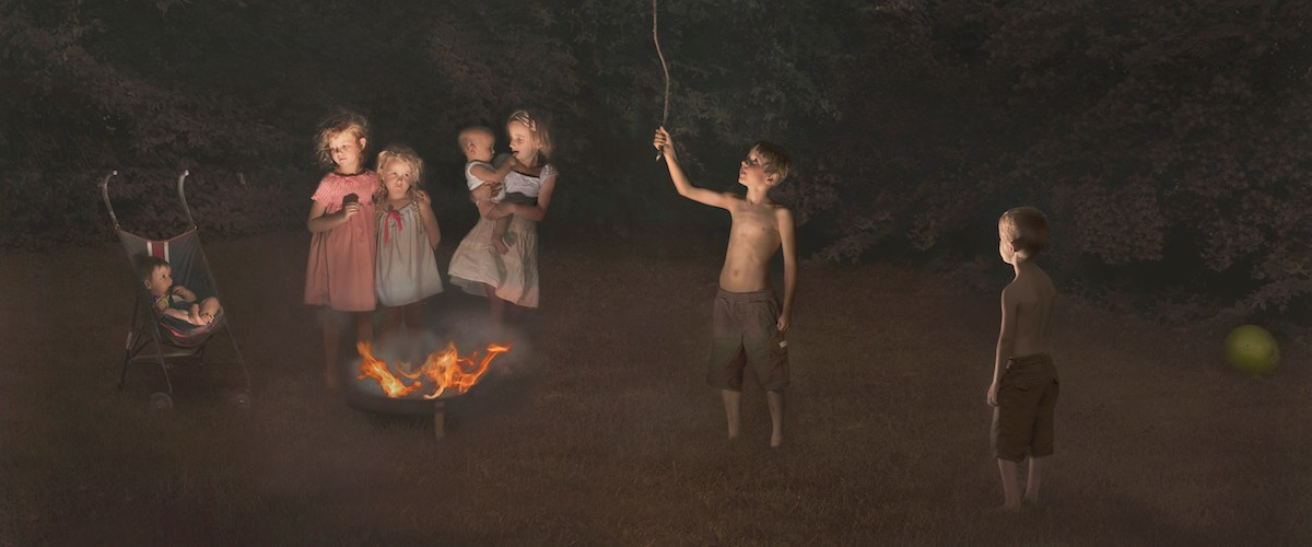 photograph by Julie Blackmon, of children around a campfie.