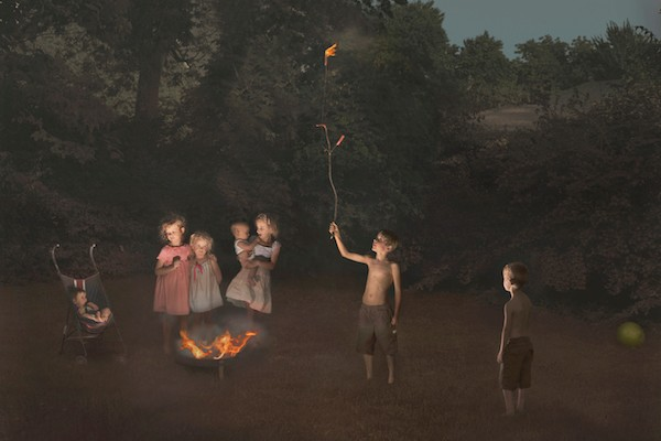 photograph by Julie Blackmon, of children around a campfire.