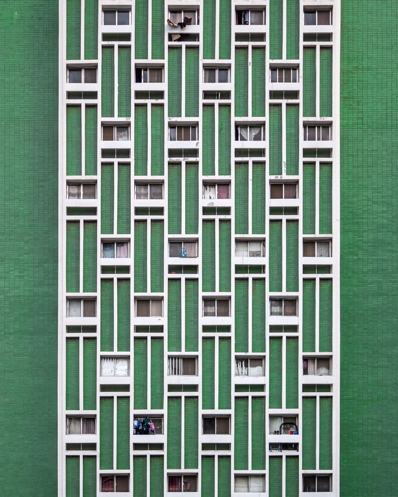 green and white facade of a building with multiple windows