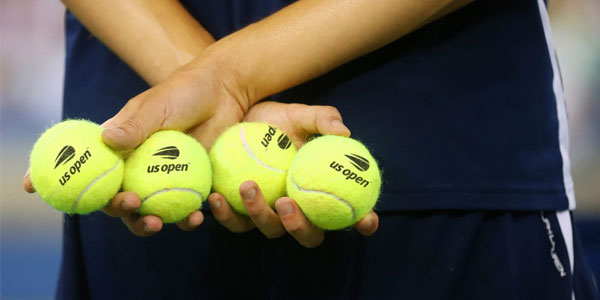 Ballboy at US Open holds tennis balls with logo by Sagi Haviv.