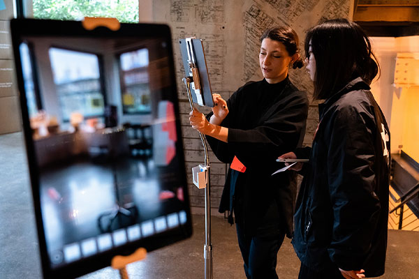 Nadine Kolodziey shows a visitor how her augmented reality illustrations work.