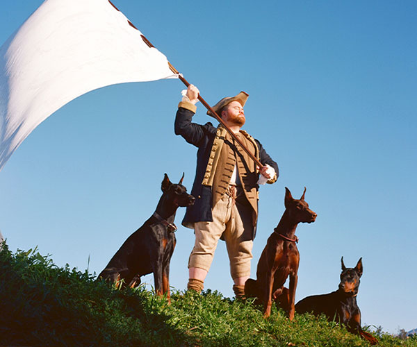 Image of man in 19th century costume waving a flag with two dogs in front of him