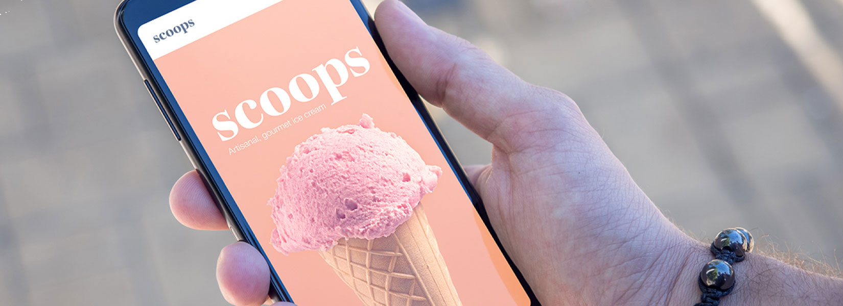 photo of a hand holding a smartphone with an ice-cream app on the screen
