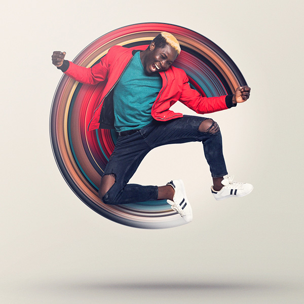 Man with red jacket jumps in air, multi-colored circle extends from his left hand to right foot