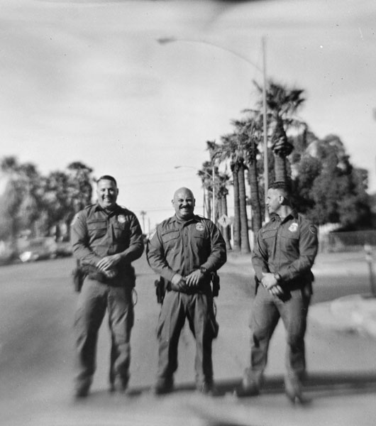 Three men in uniform stand in the nmiddle of a street in a photograph taken with an old film camera with a handmade lens.