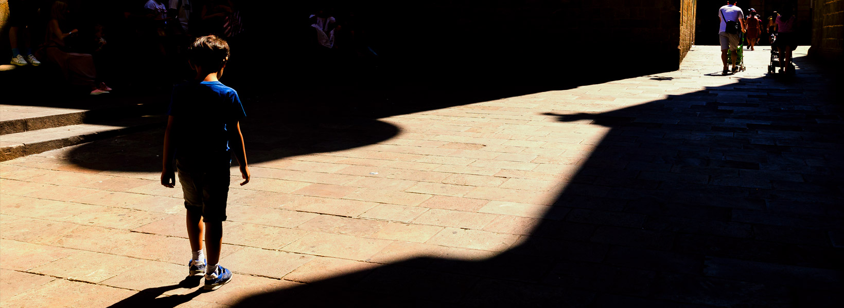 Photograph of a young boy walking in a patch of light in Barcelona's Gothic Quarter