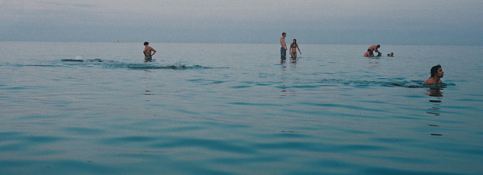 A photo of people bathing in calm, blue water