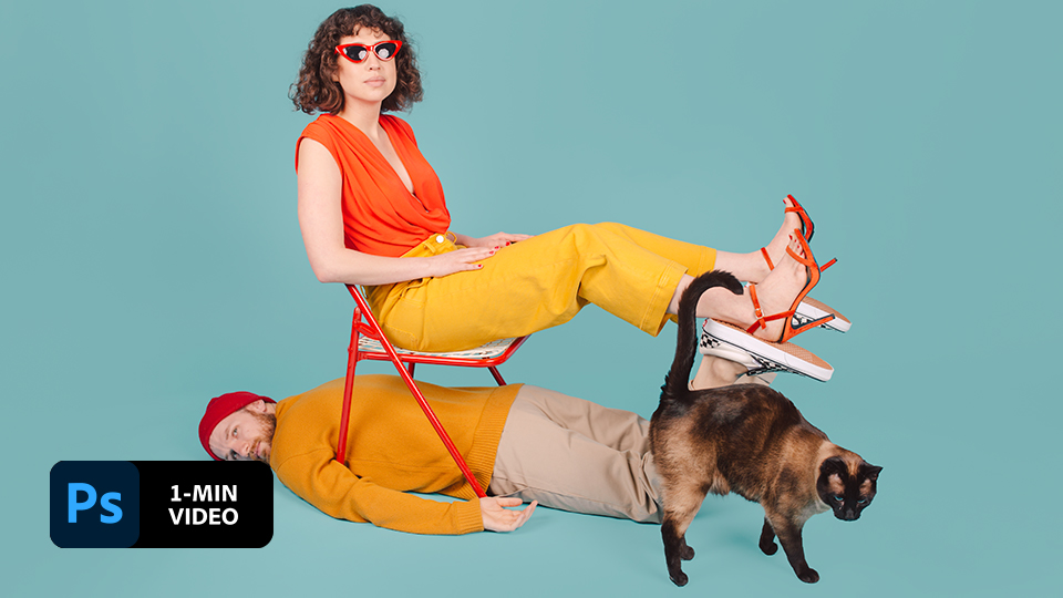 Woman with bright clothes sits on chair while man with bright clothes lays underneath against a blue backdrop