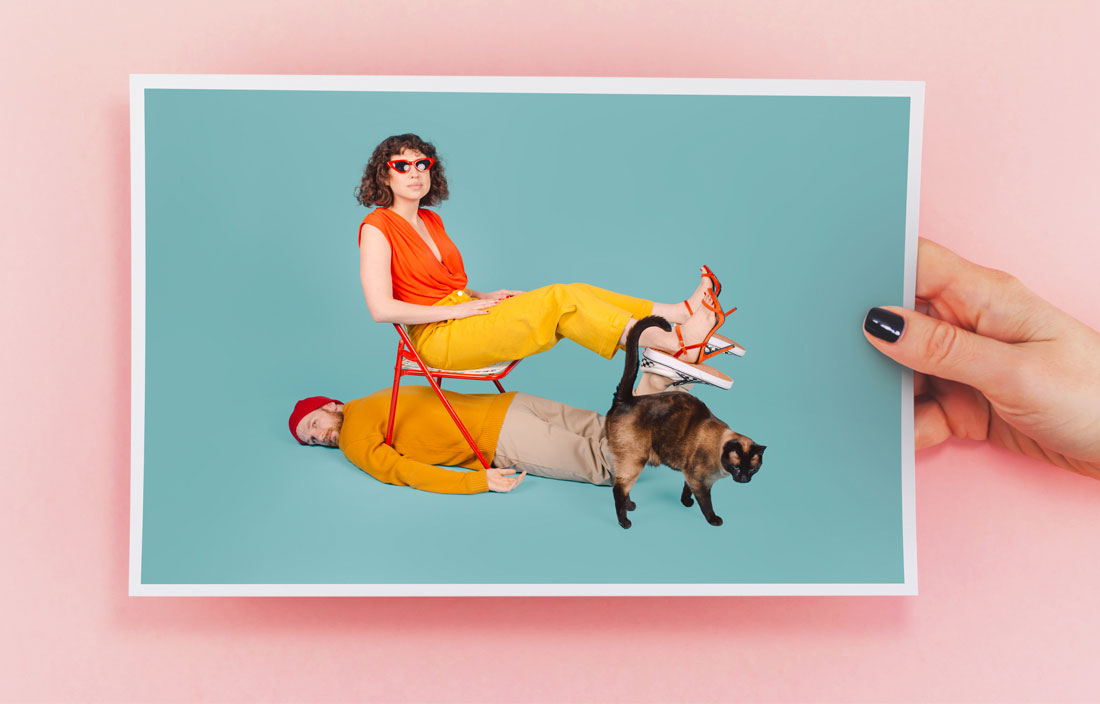 Image of models and cat against teal background placed on photo paper held against a pink background