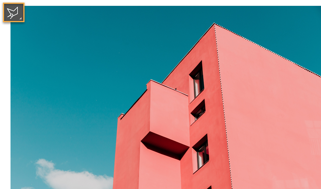 , right angle of coral pink building against a blue sky with a cloud on the lower left