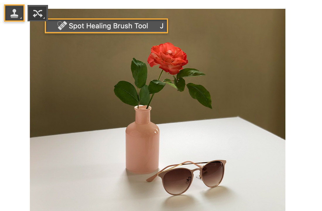 Clone Stamp and Spot Healing Brush icon displays over image of flower in vase & sunglasses on light-colored table