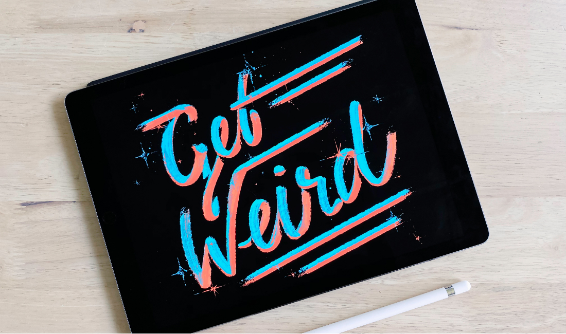 Salmon and turquoise brushed, hand lettering spells 'Get Weird' on an iPad on light-colored wood