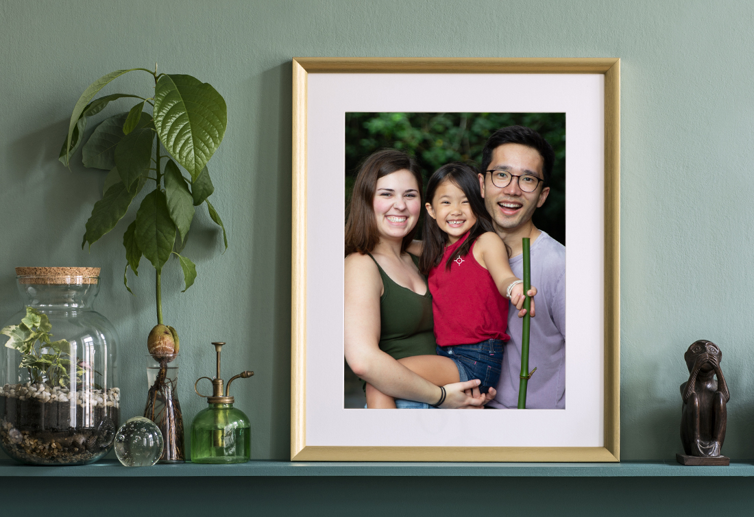 Final photo displays in gold frame on a green mantle against a green wall